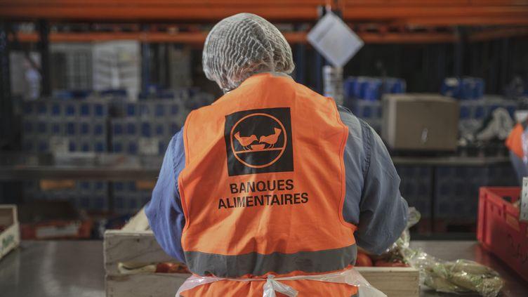 Un bénévole de la Banque alimentaire de Carcassonne prépare une caisse denourriture, le 23 novembre 2020. (IDRISS BIGOU-GILLES / HANS LUCAS)