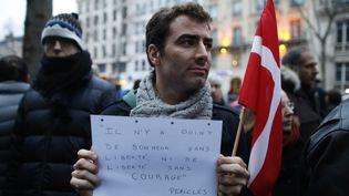 Un homme participe à un rassemblement devant l'ambassade du Danemark à Paris, le 15 février 2015, en hommage aux victimes des attentats commis à Copenhague la veille. (THOMAS SAMSON / AFP)