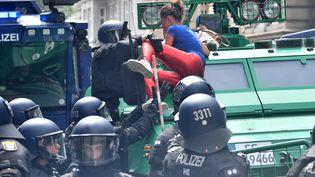 Une manifestante interpellée par la police, vendredi 7 juillet, à Hambourg (Allemagne). (BORIS ROESSLER / DPA / AFP)