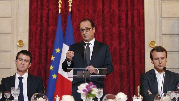François Hollande, entouré du Premier ministre, Manuel Vall,et du ministre de l'Economie, Emmanuel Macron, à l'Elysée, dimanche 19 octobre 2014. ( AFP )
