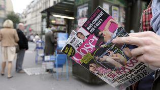 Un lecteur consulte le magazine Closer le 14 septembre 2012. (KENZO TRIBOUILLARD / AFP)