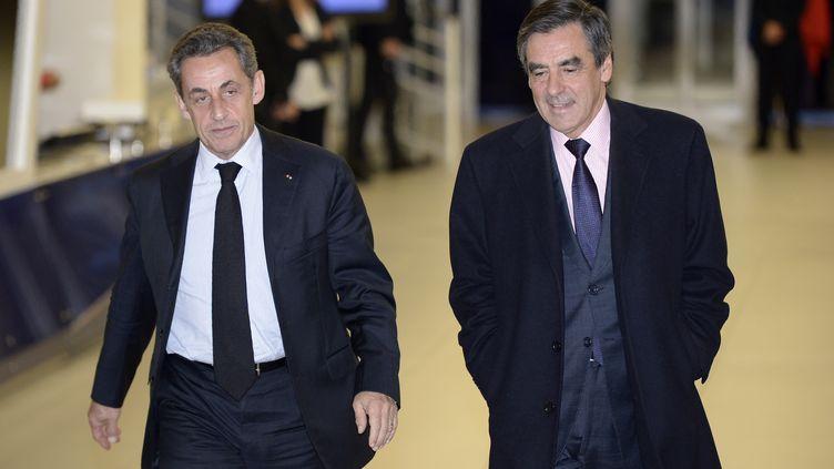 L'ancien président Nicolas Sarkozy et son ancien Premier ministre, François Fillon, quittent le siège de l'UMP après une réunion, le 2 décembre 2014, à Paris. (LIONEL BONAVENTURE / AFP)