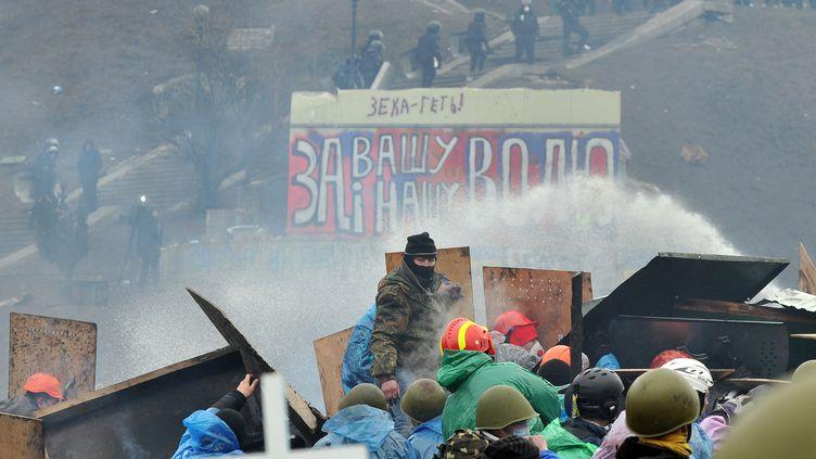 Des manifestants antigouvernementaux affrontent la police sur la place de l'Indépendance, à Kiev (Ukraine), mercredi 19 février 2014. (GENYA SAVILOV / AFP)