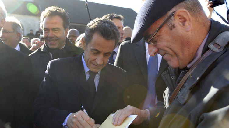 Nicolas Sarkozy signe un autographe après avoir rendu hommage au général De Gaulle à l'occasion du 41e anniversaire de sa mort,à Colombey-les-Deux-Eglises (Haute-Marne), le 9 novembre 2011. (ERIC FEFERBERG / AFP)