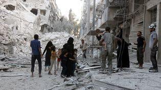 Une famille syrienne quitte ce quartier d'Alep après un bombardement aérien le 23 septembre 2016. (THAER MOHAMMED / AFP)