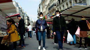 Un couple déambule dans les allées d'un marché à Montmartre (Paris), le 22 mars 2020. (EDOUARD RICHARD / HANS LUCAS)
