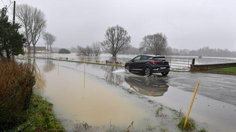Une voiture roule sur une route inondée à Caudescure (Nord). (MAXPPP)