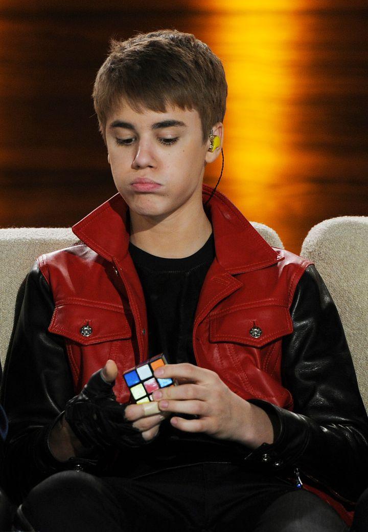 Le chanteur canadien Justin Bieber tente de résoudre un casse-tête lors d'une émission de télévision allemande, le 19 mars 2011, à Augsbourg (Allemagne). (CHRISTOF STACHE / AFP)