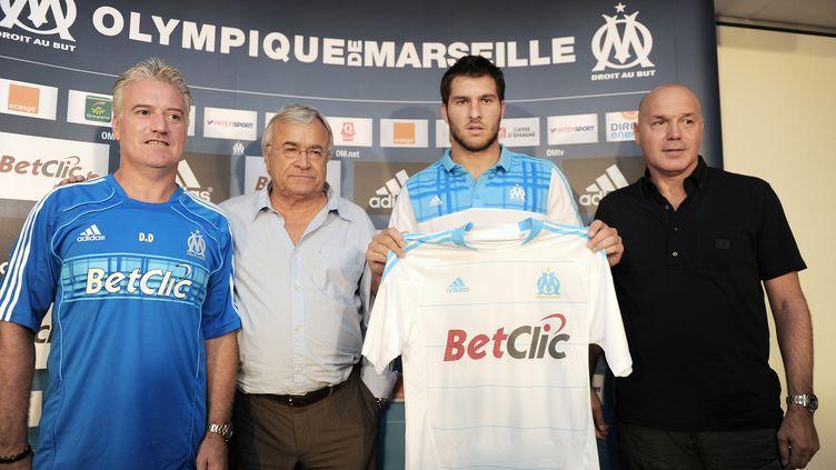 L'entraîneur de l'Olympique de Marseille, Didier Deschamps, le président du club, Jean-Claude Dassier, et le manager sportif, José Anigo, autour d'André-Pierre Gignac, le 24 août 2010 à Marseille (Bouches-du-Rhône), à l'occasion de son arrivée au club. (GERARD JULIEN / AFP)