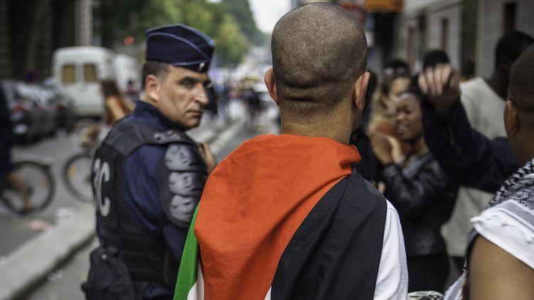 Un policier et un manifestant portant un drapeau palestinien, pendant le rassemblement pro-Gaza interdit à Paris, le 19 juillet 2014. (GUILLAUME GEYNET / CITIZENSIDE / AFP)
