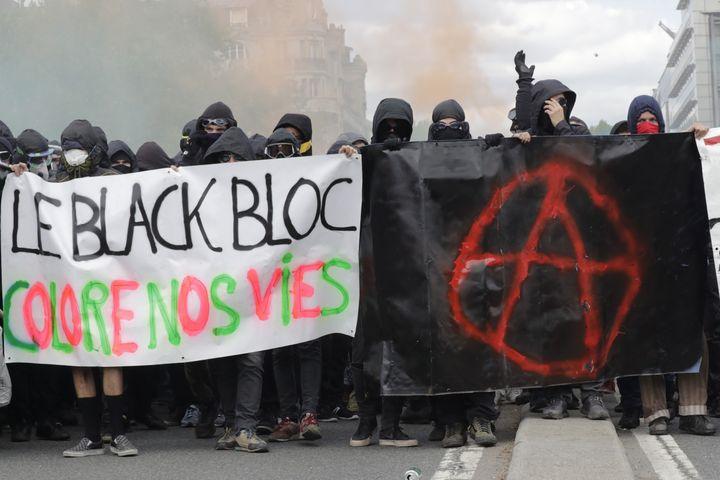 Des militants cagoulés à hauteur du pont d'Austerlitz, à Paris, lors des manifestations du 1er mai 2018. (THOMAS SAMSON / AFP)
