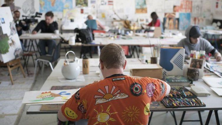 Erich Tressler travaille sur ses dessins au centre d'art brut Gugging, en Autriche.  (JOE KLAMAR / AFP)