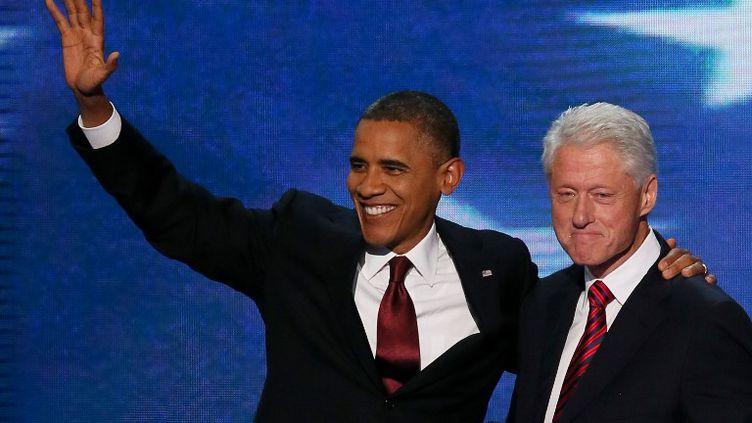 Le président américain sortant Barack Obama (G) et Bill Clinton (D), dernier président démocrate avant lui, se rejoignent sur scène, le 5 septembre 2012 à Charlotte (Caroline du Nord). (ALEX WONG / GETTY IMAGES NORTH AMERICA / AFP)