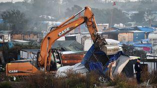 """Un engin de chantier déblaie des cabanes, dans la """"jungle"""" de Calais, le 27 octobre 2016. (PHILIPPE HUGUEN / AFP)"""