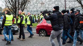"""Un policier de la brigade anticriminalité pointe unflash-ballen direction de """"gilets jaunes"""", le 29 décembre 2018, à Lille, lors d'une manifestation. (JULIE SEBADELHA / HANS LUCAS / AFP)"""