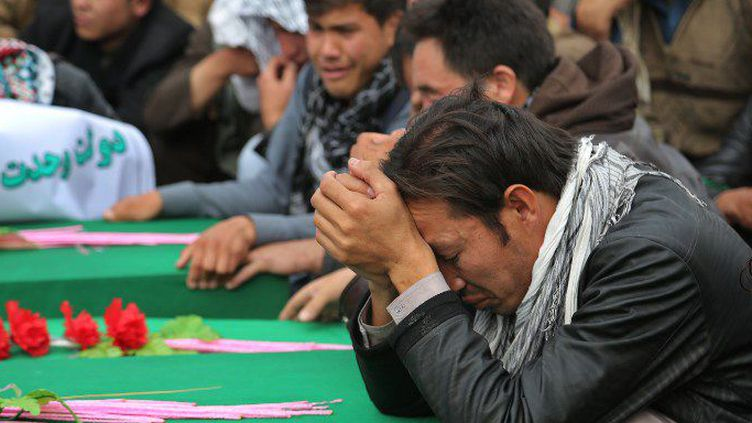 Dans la province afghane de Ghazni, des Hazaras se recueillent, le 10 novembre 2015, sur les cercueils de victimes chiites décapitées par Daech. (AFP PHOTO / Rahmatullah Alizadah)