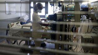 Une soignante s'occupe d'un patient atteint du Covid-19 dans le service de réanimation de l'hôpital de Saint-Pierre, à La Réunion, le 30 juillet 2021. (RICHARD BOUHET / AFP)