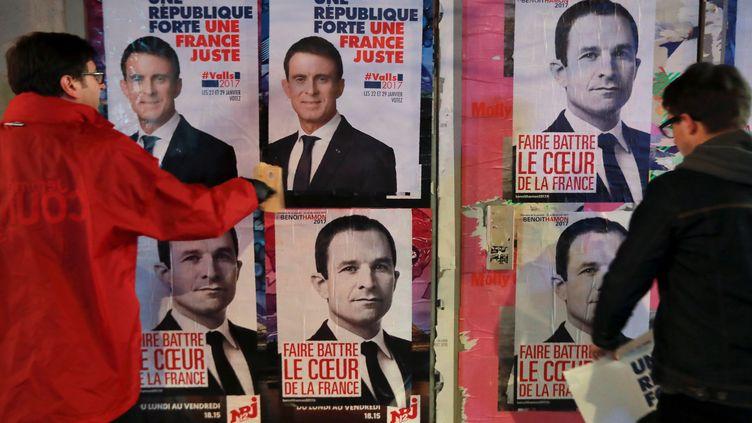 Des militants de Manuel Valls et Benoît Hamon collent des affiches de campagne des deux candidats à la primaire de la gauche, le 11 janvier 2017 à Paris. (JACQUES DEMARTHON / AFP)
