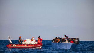 """Une photo distribuée par l'ONG Sea-Eye et prise le 6 avril 2020, montre des membres de l'ONG lors d'une opération de sauvetage de réfugiés au large des côtes libyennes, avant de les amener à bord de leur navire """"Alan Kurdi"""" (photo d'illustration). (CEDRIC FETTOUCHE / AFP)"""