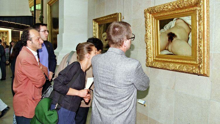 """Des visiteurs devant le tableau de Gustave Courbet """"L'Origine du monde"""" exposé au musée d'Orsay à Paris. (PASCAL GUYOT / AFP)"""