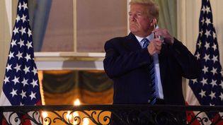 Le président Donald Trump, alors souffrant du Covid-19, se présente àla presse depuis son balcon, le 5octobre 2020. (NICHOLAS KAMM / AFP)