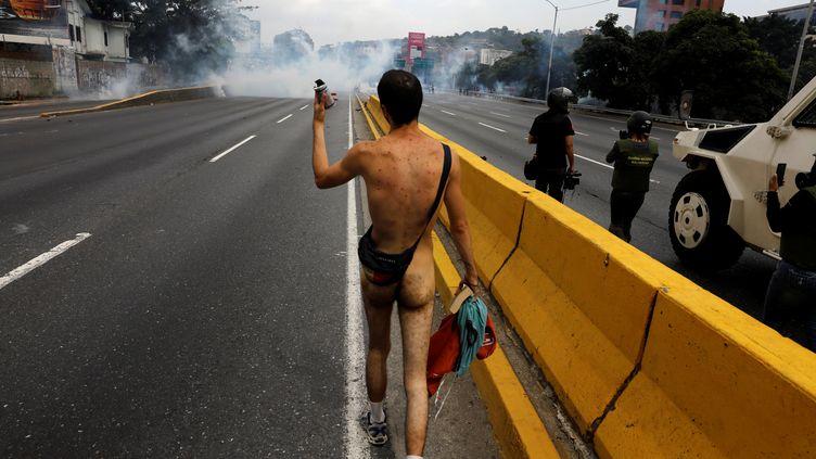 Un manifestant nu brave les forces de l'ordre le 20 avril 2017 à Caracas (Venezuela). (CARLOS GARCIA RAWLINS / REUTERS)