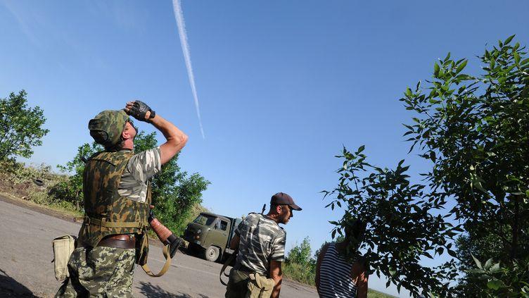 Des rebelles pro-russes observent des avions de l'armée ukrainienne qui survolent la ville de Marynivka, près de Donetsk, dans l'est de l'Ukraine, mercredi 16 juillet 2014. (DOMINIQUE FAGET / AFP)
