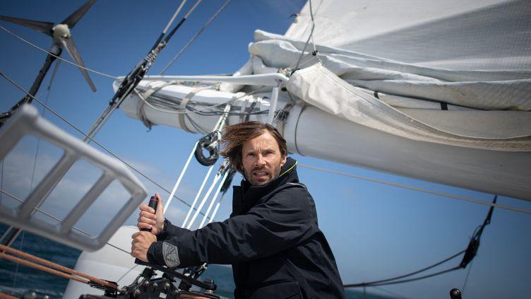 """Le skipper français Romain Pilliard sur son trimaran, """"Use it again"""", le long des côtes de la Trinité-sur-Mer, le 25 mai 2021. En 2016, il a décidé de retaper l'ancien trimaran de classe Ultim d'Ellen Mac Arthur, selon les principes de l'économie circulaire : Reduce, ReUse et Recycle.  (LOIC VENANCE / AFP)"""