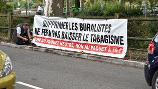 Un buraliste installe une bannière pour protester contre la hausse des prix du tabac, le 17 juillet 2017, à Toulouse. (REMY GABALDA / AFP)