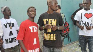 """Malal Tall, alias Fou malade (en tee-shirt rouge), l'un des leaders du collectif sénégalais """"Y en a marre"""", au moment du lancement du mouvement en juin 2011. (SEYLLOU / AFP)"""