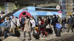 Des passagers passent devant un train Ouigo, dans la gare Montparnasse, à Paris, le 12 mai 2021. (JACOPO LANDI / HANS LUCAS / AFP)