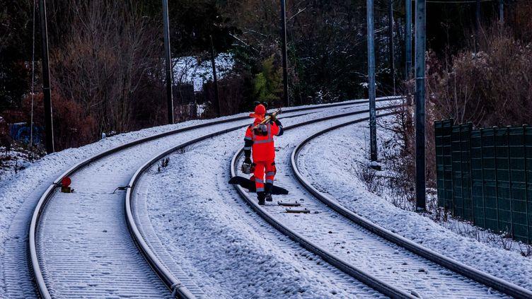 Un ouvrier travaille sur les voies ferrées sous la neige. Photo d'illustration. (MAXPPP)