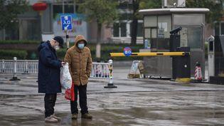 Deux personnes portent des masques face à l'un des centres de traitement du virus à Wuhan, dans la province du Hubei (Chine), le 24 janvier 2020. (HECTOR RETAMAL / AFP)