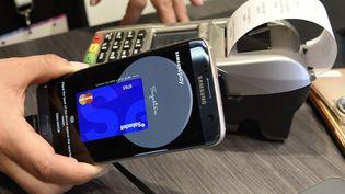 Une personneexposant le système de paiement sans contact Samsung Pay au Mobile World Congress (MWC) de Barcelone, en février 2017. (LLUIS GENE / AFP)