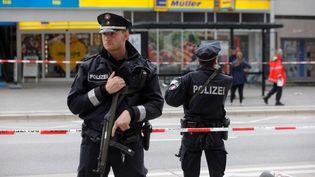 Des policiers allemands devant un supermarché de Hambourg (Allemagne) après l'attaque d'un homme armé d'un couteau qui a fait un mort, le 28 juillet 2017. (MARKUS SCHOLZ / DPA)