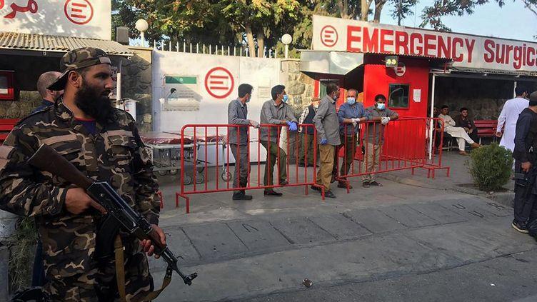 Un taliban, armé, surveille l'entrée d'un hôpital qui prend en charge les blessés après une explosion à Kaboul (Afghanistan), le 3 octobre 2021. (HOSHANG HASHIMI / AFP)