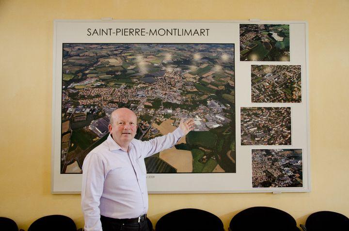 Le maire de Saint-Pierre-Montlimart (Maine-et-Loire), Serge Piou, devant une photo de la ville, le 15 avril 2015. Le bois juste au-dessus de sa main correspond à la zone inconstructible à cause des galeries de l'ancienne mine. (THOMAS BAIETTO / FRANCETV INFO)