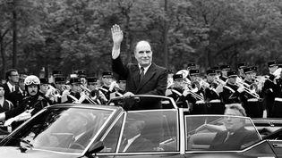 François Mitterrand salue la foule qui l'acclame alors qu'il remonte les Champs Elysées lors de sa cérémonie d'investiture,le 21 mai 1981 à Paris. (- / AFP)
