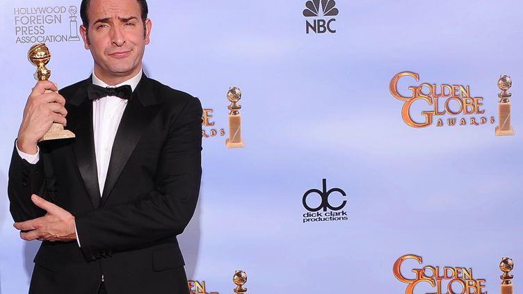 """Jean Dujardin pose avec son Golden Globe du meilleur acteur de comédie, reçu pour sa prestation dans le film """"The Artist"""" de Michel Hazanavicius, à Beverly Hills (Californie), le 15 janvier 2012. (ROBYN BECK / AFP)"""