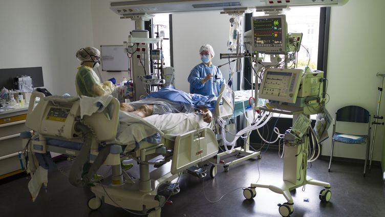Des soignants sont au chevet d'un patient en réanimation à l'hôpital Louis-Pasteur de Colmar (Haut-Rhin), le 26 mars 2020. (SEBASTIEN BOZON / AFP)