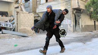 Un Casque blanc syrien porte un homme blessé dans les bombarbements à Alep, en novembre 2016. (AMEER ALHALBI / AFP)