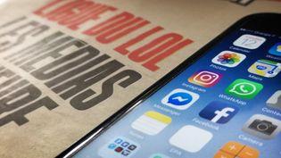 """Un exemplaire du journal Libération dont la Une porte sur la """"Ligue du LOL"""" à côté d'un smartphone (ETIENNE LAURENT/EPA/Newscom/MaxPPP)"""