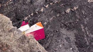 Un des débris de l'Airbus A320 retrouvés sur les lieux du crash, dans les Alpes-de-Haute-Provence. (DENIS BOIS / AFPTV)