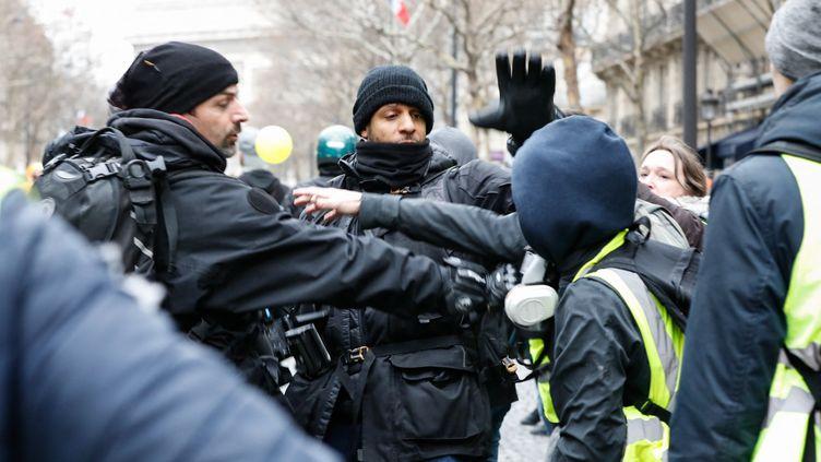 """Des journalistes sont pris à partie par des """"gilets jaunes"""", le 12 janvier 2019, près de la place de l'Etoile, à Paris. (LAURE BOYER / HANS LUCAS / AFP)"""