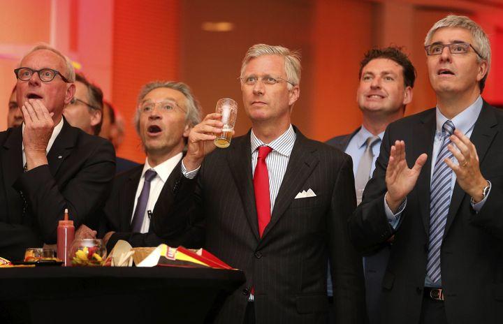 Philippe de Belgique sirote une bière devant un écran géant, le 17 juin à Bruxelles, lors de la rencontre entre la Belgique et l'Algérie. (NICOLAS MAETERLINCK / BELGA MAG / AFP)