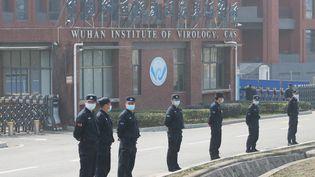 Des agents de sécurité devant l'Institut de virologie de Wuhan (Chine), le 3 février 2021. (KOKI KATAOKA / AFP)