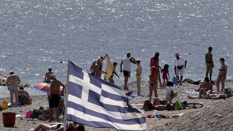 Des touristes sur une plage à Athènes, le 28 juin 2015. (LOUISA GOULIAMAKI / AFP)