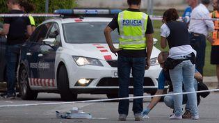 Des officiers des Mossos d'Esquadra, la police catalane, inspectent les environs de la morgue à Gava, près de Barcelone (Espagne), où un homme a tué deux policiersle 6 juillet 2017. (JOSEP LAGO / AFP)