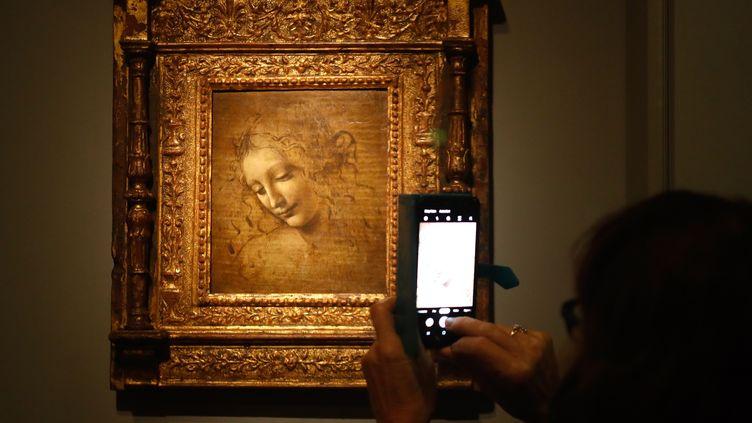 """Une personne prenant en photo """"LaScapigliata"""" de Léonard de Vinciau musée du Louvre, le 22 octobre 2019. (FRANCOIS GUILLOT / AFP)"""