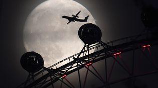 """Un avion est photographié au desus du manège """"London Eye"""" à Londres (Angleterre), la veille de la """"super Lune"""", le 13 novembre 2016.  (TOBY MELVILLE / REUTERS)"""